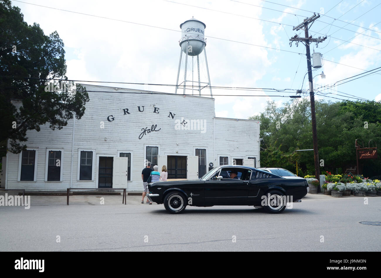 a black classic mustang passes in front of gruene hall texas - Stock Image