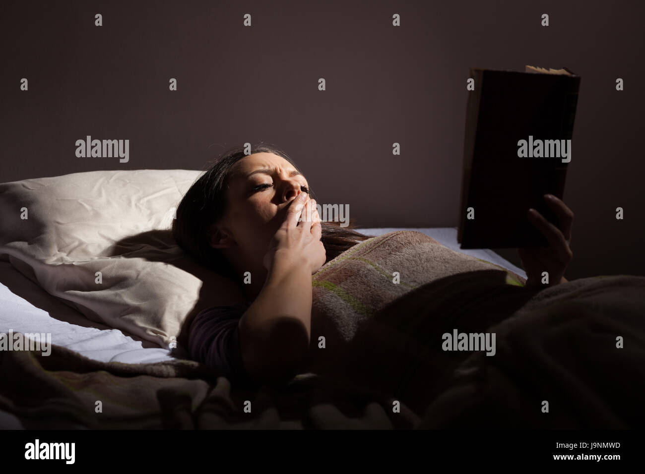 Young woman is reading a book before sleep. - Stock Image