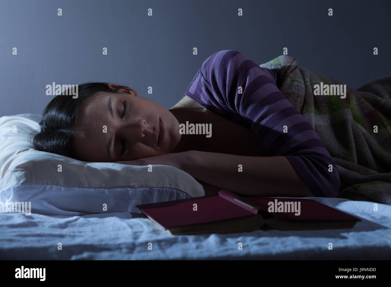 Young woman is sleeping in her bed - Stock Image