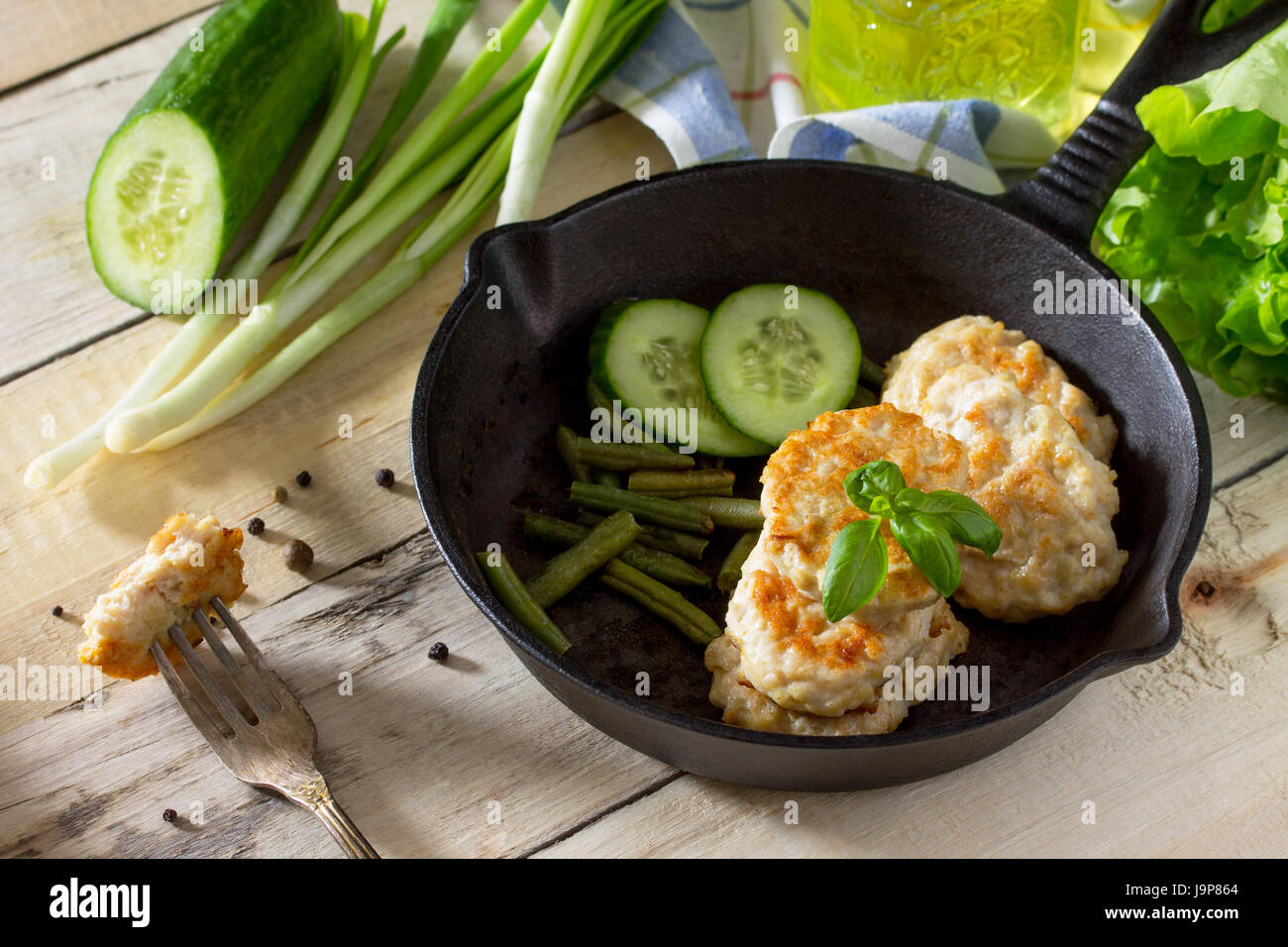Meat cutlet from minced meat, served in a cast-iron frying pan with green beans kitchen table in a rustic style. - Stock Image