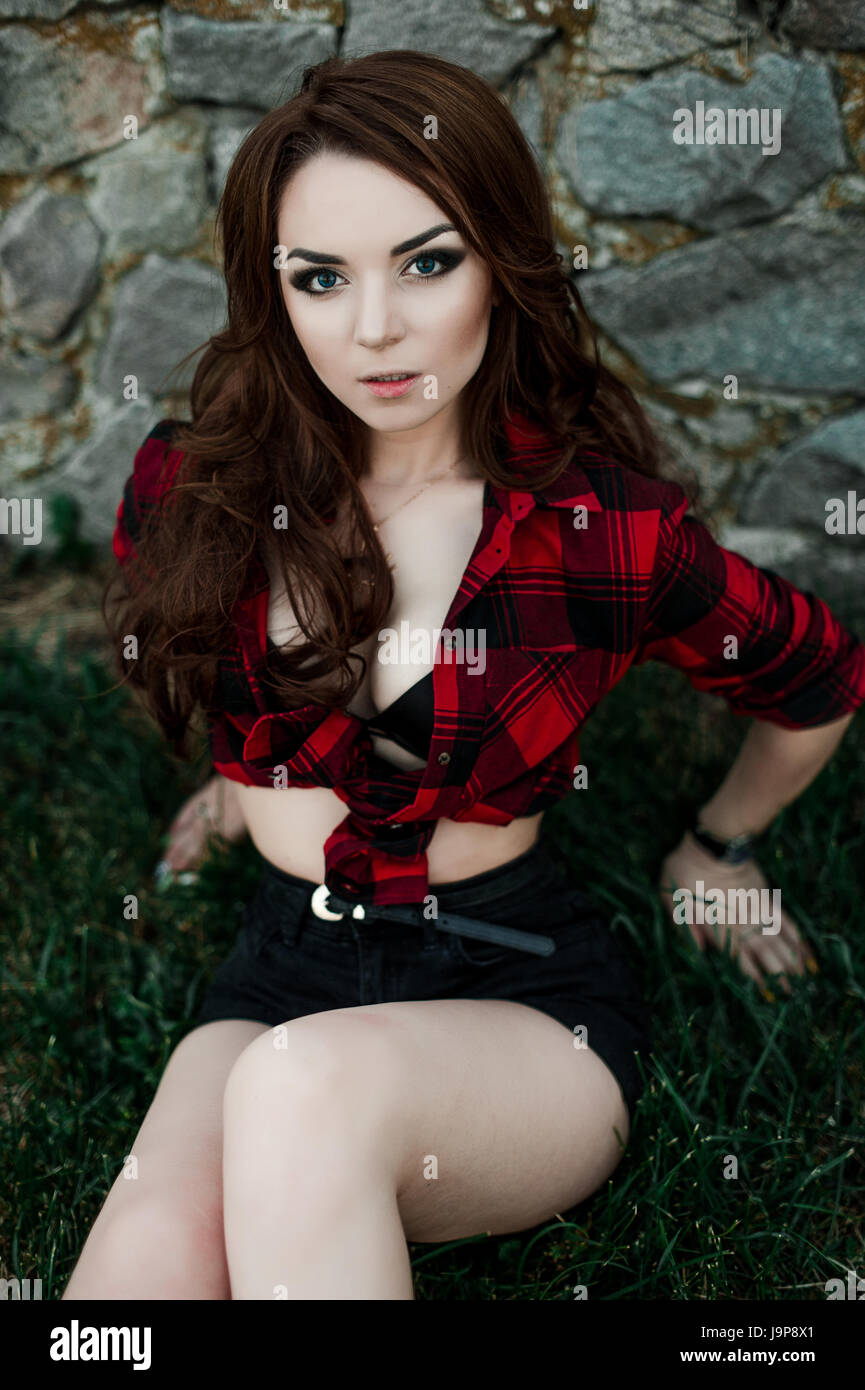 dc1a0b73143 Beautiful young hipster girl posing and smiling near urban wall background  in red plaid shirt