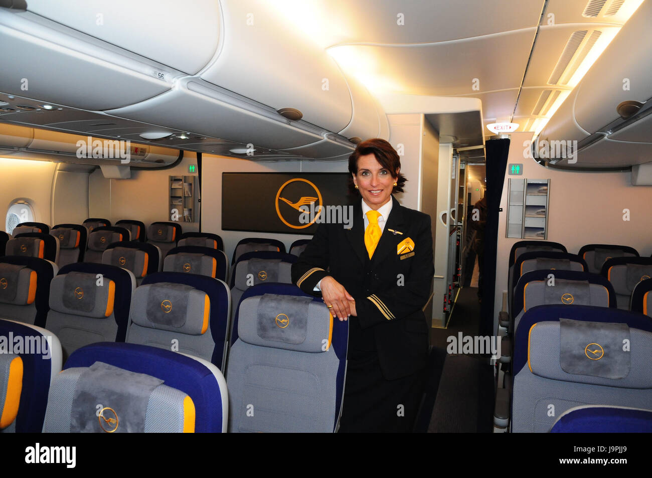 Airplane,inside,seats,flight attendant,air liner,seats,places,lighting,travel,vacation,people,stewardess,stand,smile,uniform,occupation,Lufthansa, - Stock Image
