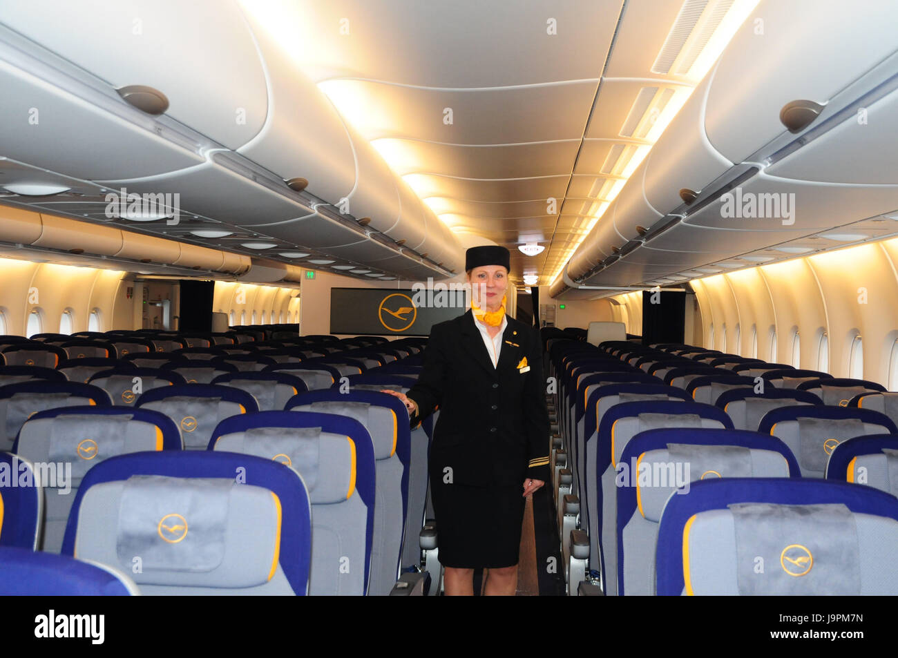 Airplane,inside,seats,flight attendant,air liner,seats,places,lighting,travel,vacation,people,stewardess,stand,smile,uniform,headgear,occupation,Lufthansa, - Stock Image
