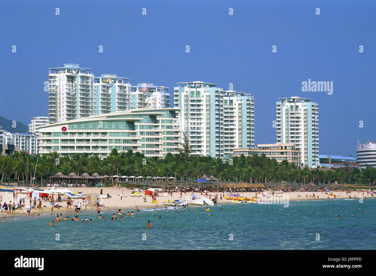China,Hainan Iceland,Sanya,Dadonghai Beach,high rises,Asia,Eastern Asia,destination,beach,sandy beach,palms,people,vacationers,tourists,vacation,rest,beach - Stock Image