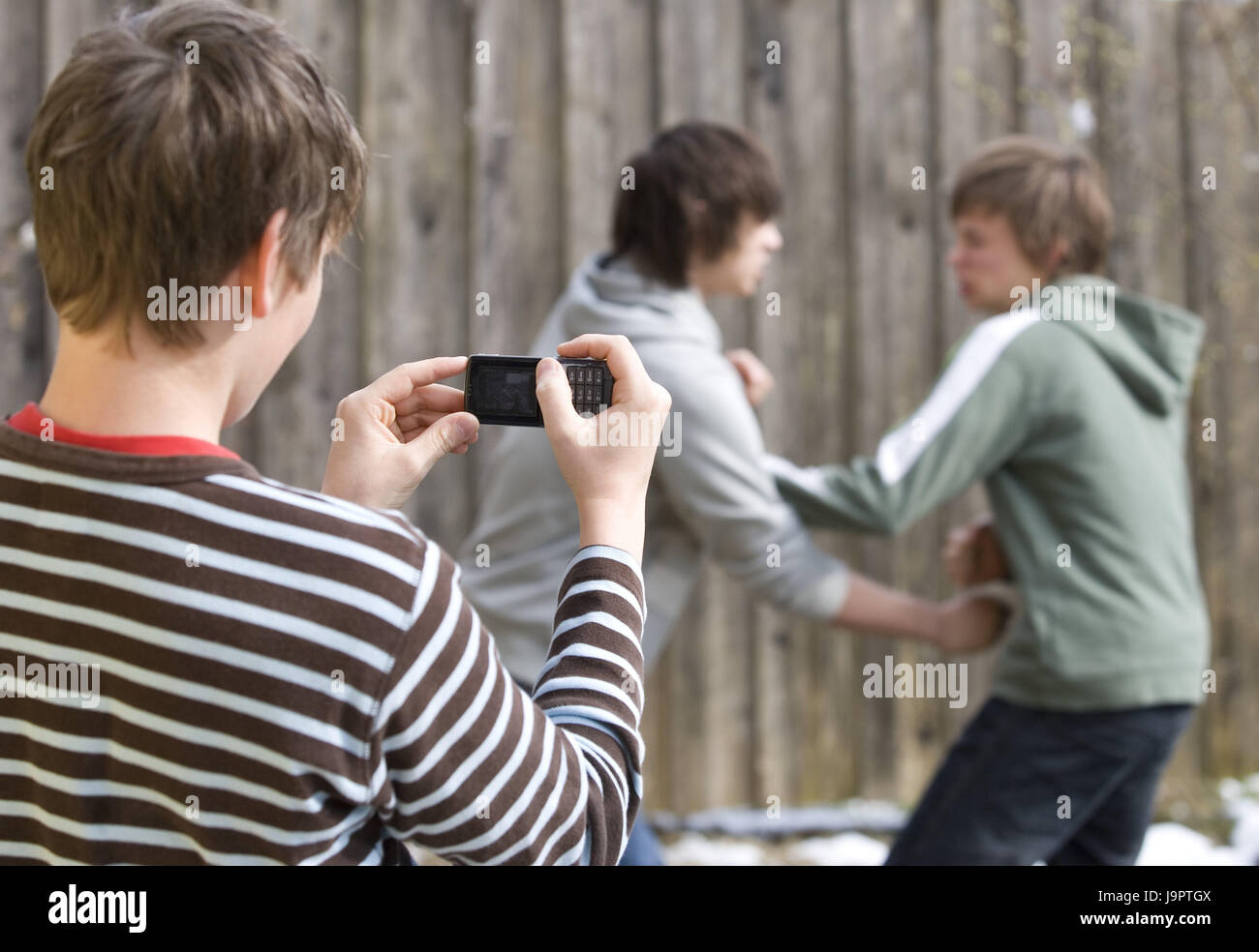 Young persons,aggression,fight,mobile phone,film,blur,boy,teenager,youth,fury,violent,fight,scuffle,fight,enemies,rivals,rage,fight,fight,outside,power,action,phone,camera - Stock Image