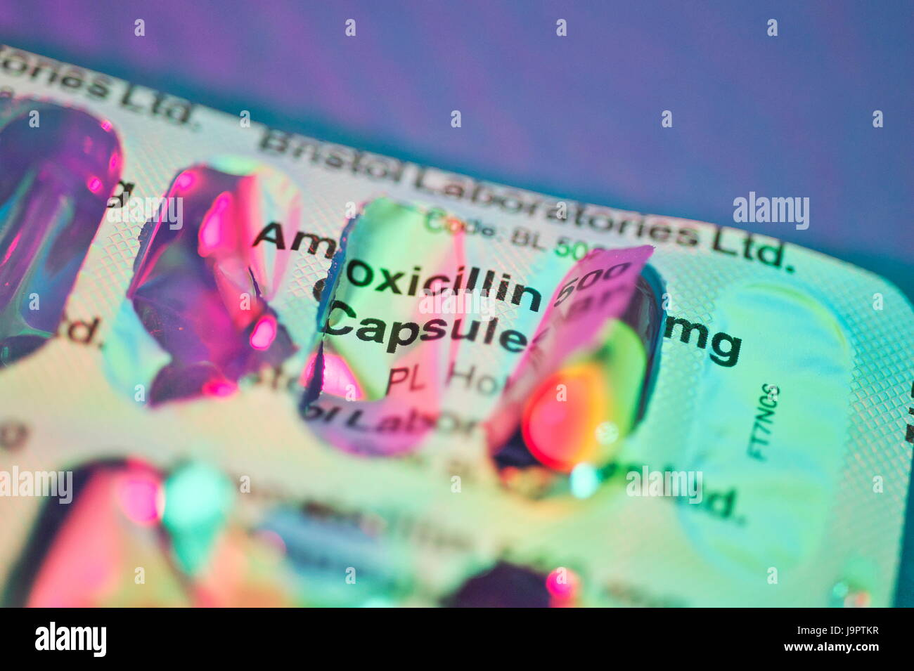 Still life dramatic lighting of Amoxicillin tablets in and out of packets, used for bacterial infections - Stock Image