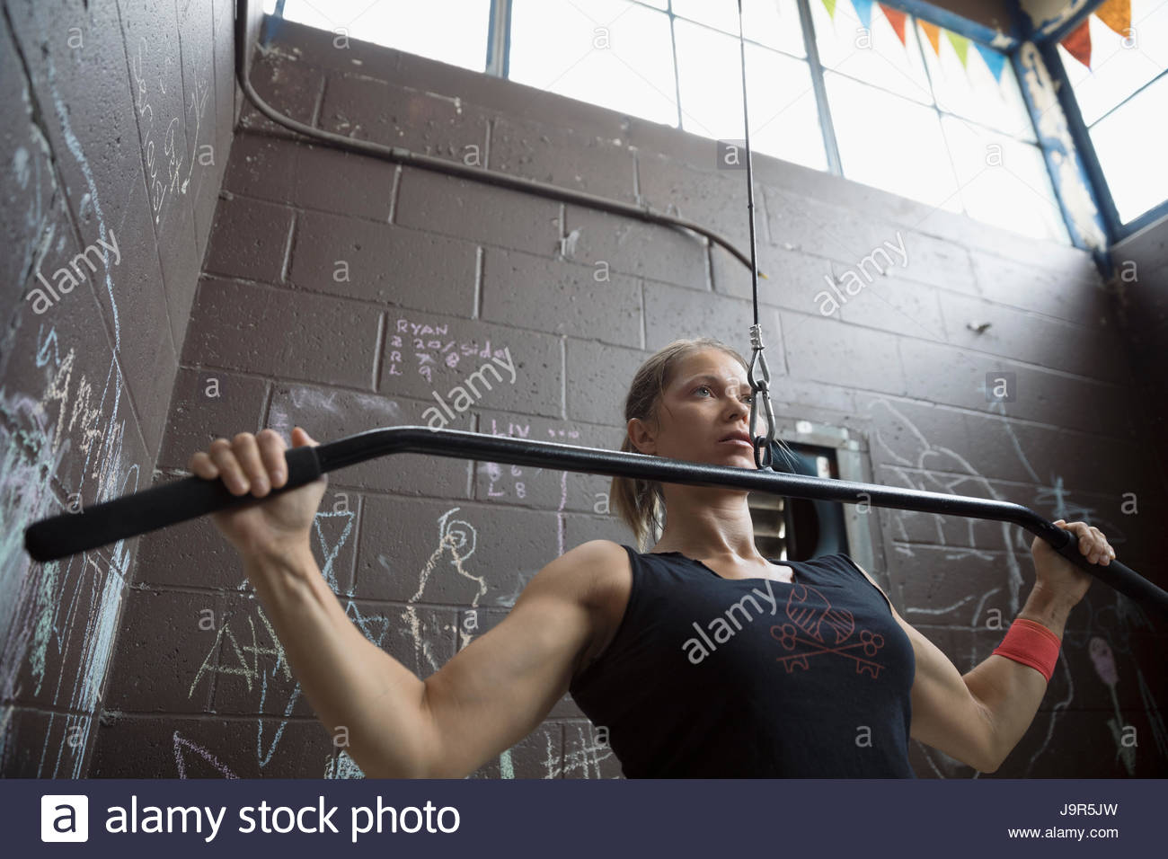 Fit woman weightlifting, doing pull downs in gritty gym - Stock Image