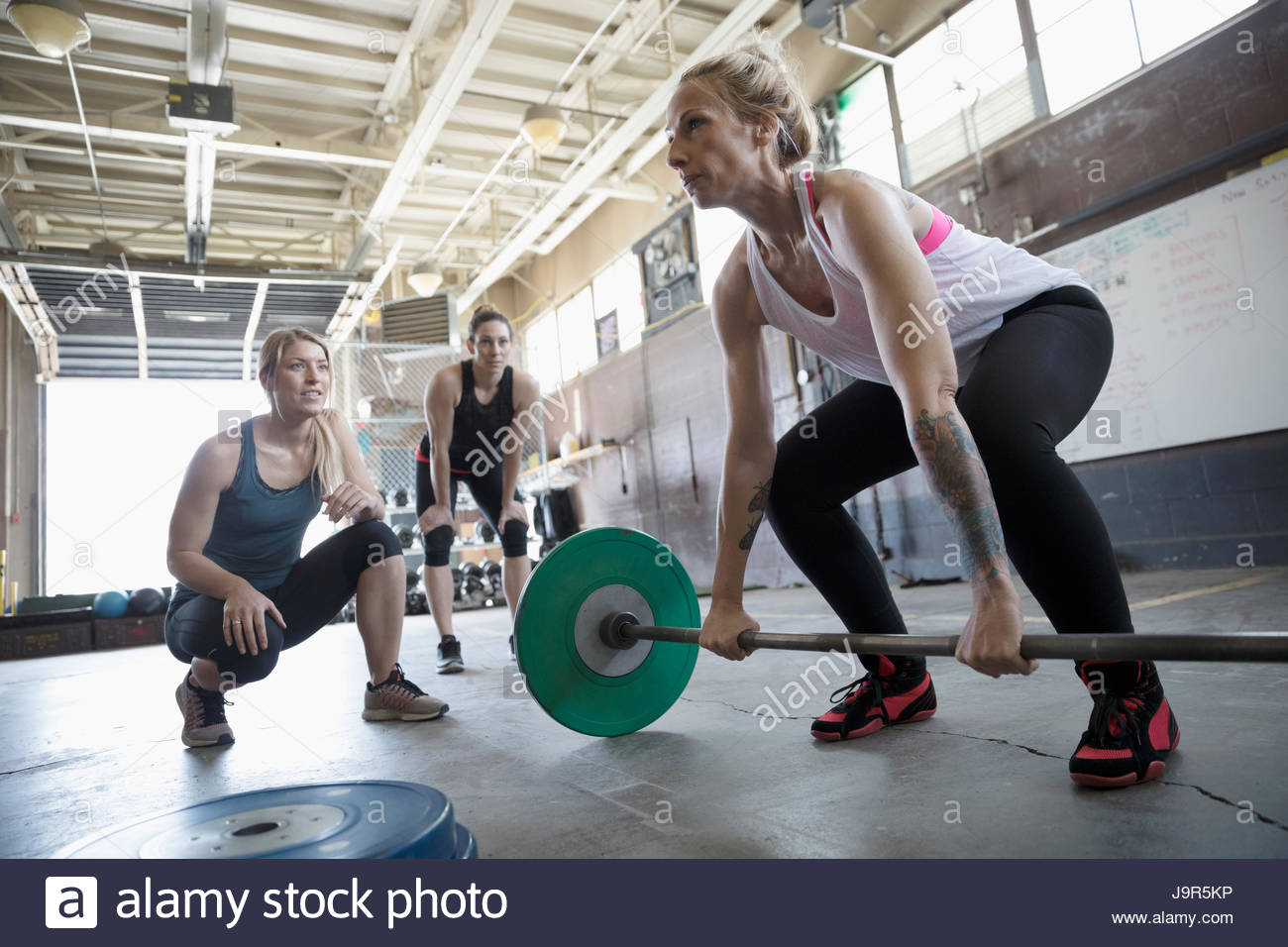 Women motivating friend weightlifting, doing barbell deadlift at gritty gym - Stock Image
