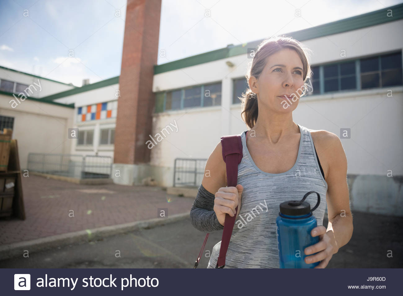 Confident, determined woman with water bottle in parking lot post workout - Stock Image