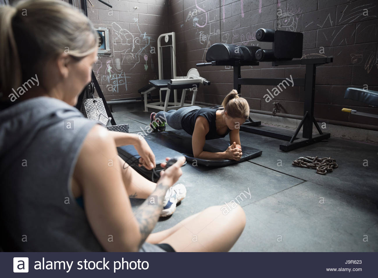 Personal trainer timing female client doing plank exercise in gritty gym - Stock Image