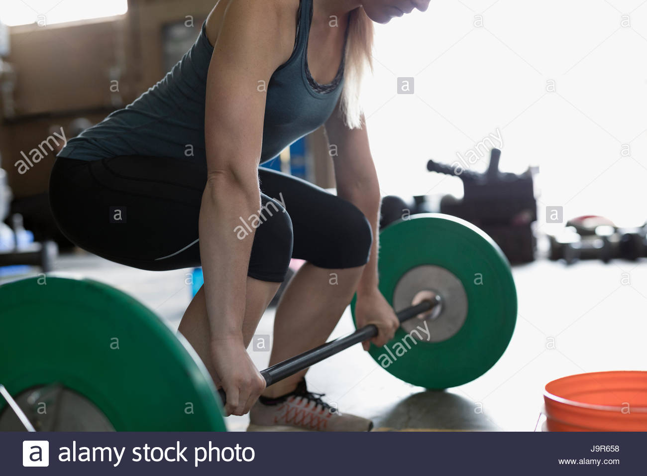 Strong woman weightlifting, doing barbell deadlift at gym Stock Photo