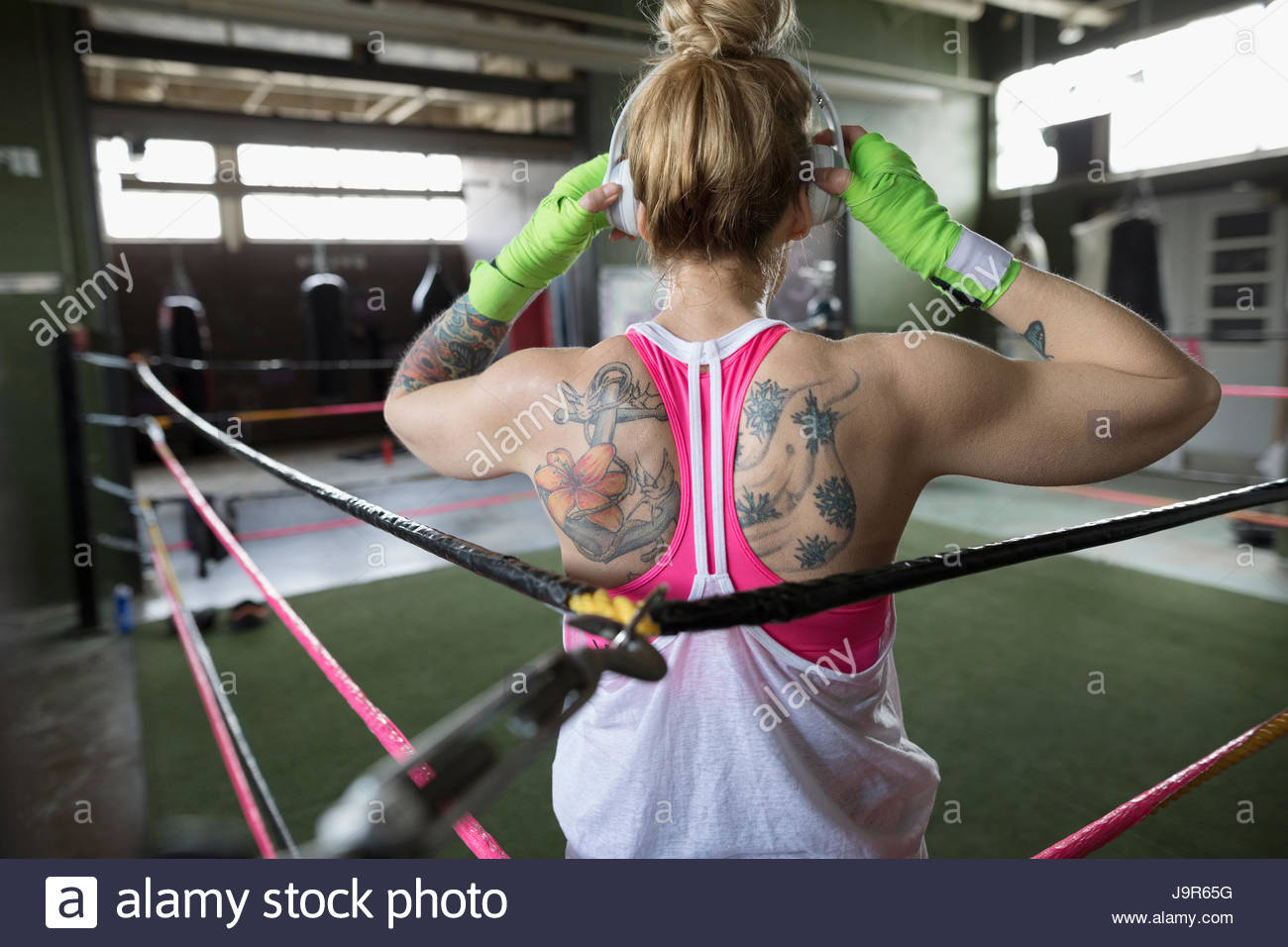 Rear view tattooed woman boxer listening to music with headphones in boxing ring at gym - Stock Image