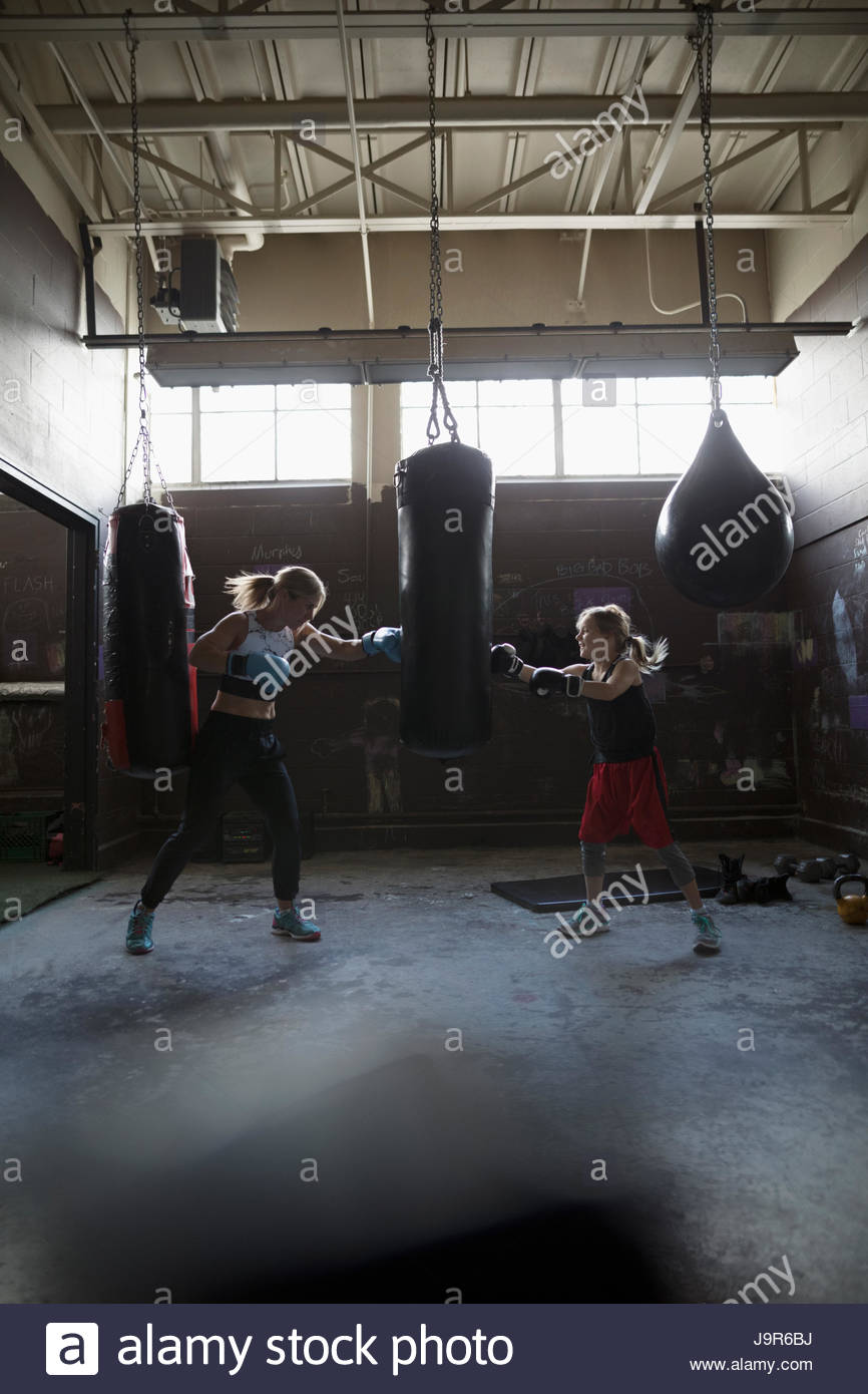 Mother and daughter boxers boxing at punching bag at gym - Stock Image