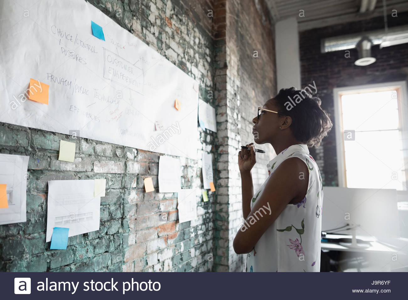 Creative businesswoman brainstorming, reviewing flow chart hanging on brick wall in office - Stock Image