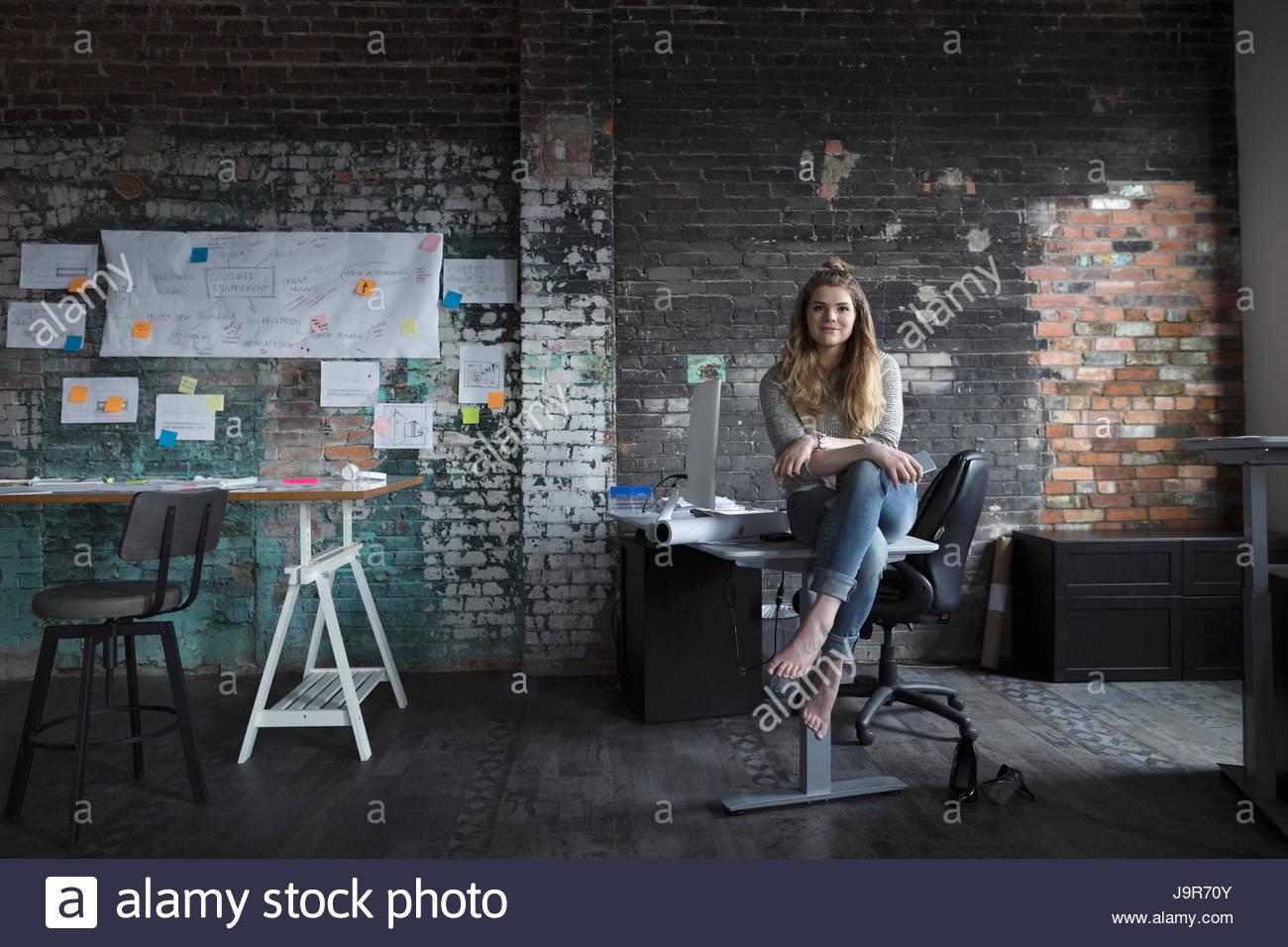 Portrait confident barefoot creative businesswoman sitting on desk in office - Stock Image