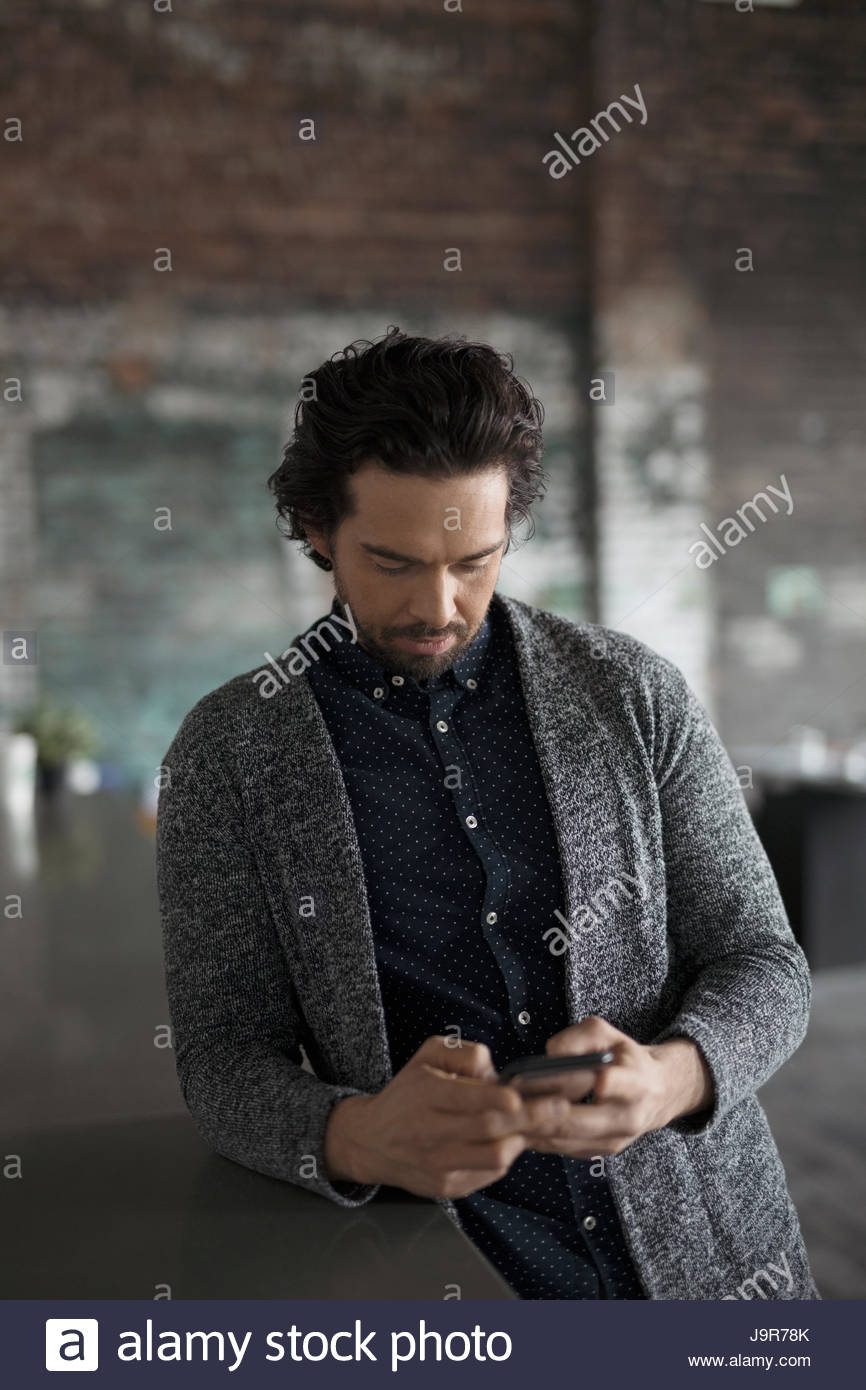 73c98268bcf Creative businessman texting with smart phone in office - Stock Image