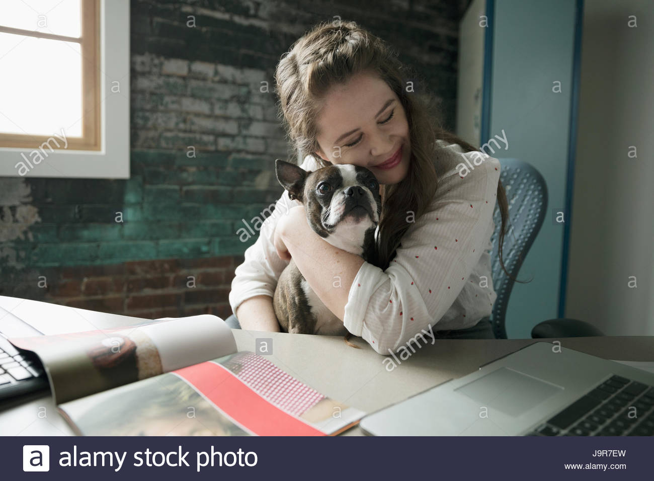 Smiling creative businesswoman hugging dog in lap at desk - Stock Image