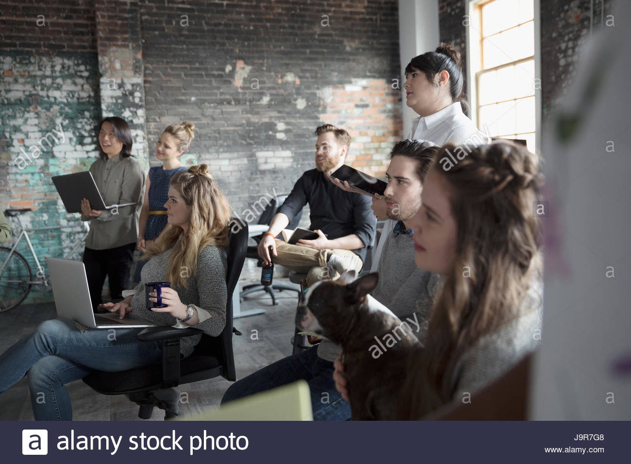 Attentive creative business people listening in meeting - Stock Image