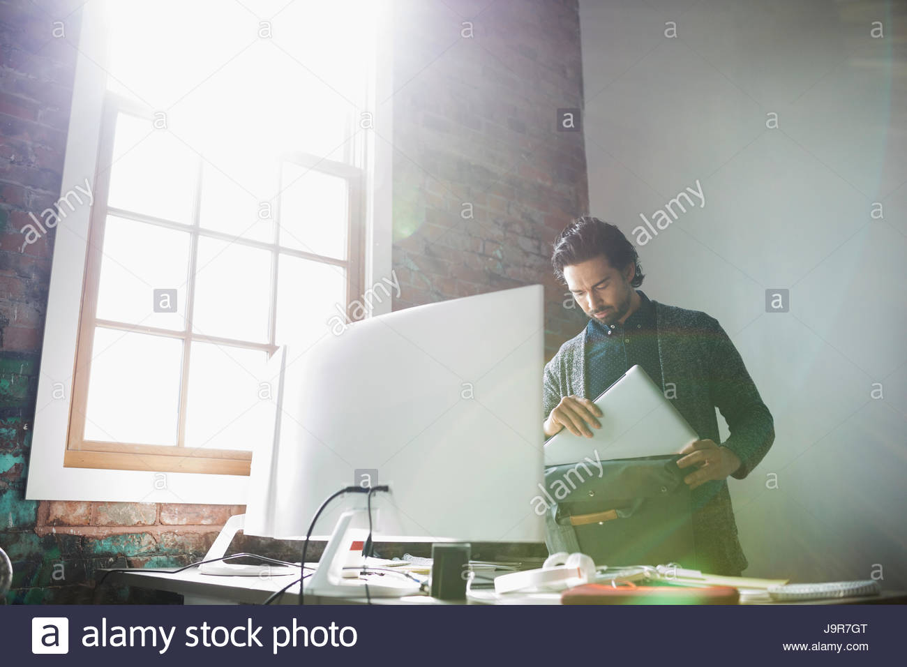 Creative businessman placing laptop in bag in sunny office - Stock Image