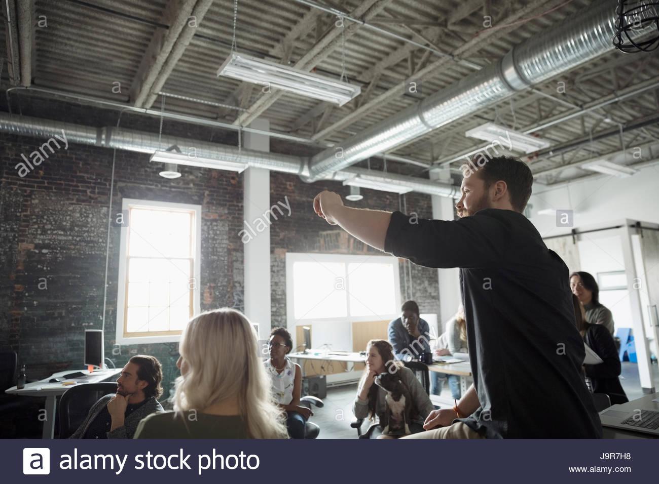 Creative businessman leading meeting in open plan loft office - Stock Image