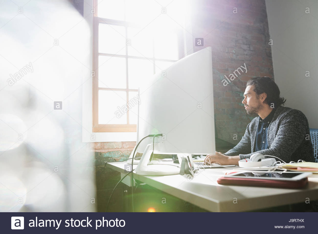 Creative businessman working at computer in sunny office - Stock Image