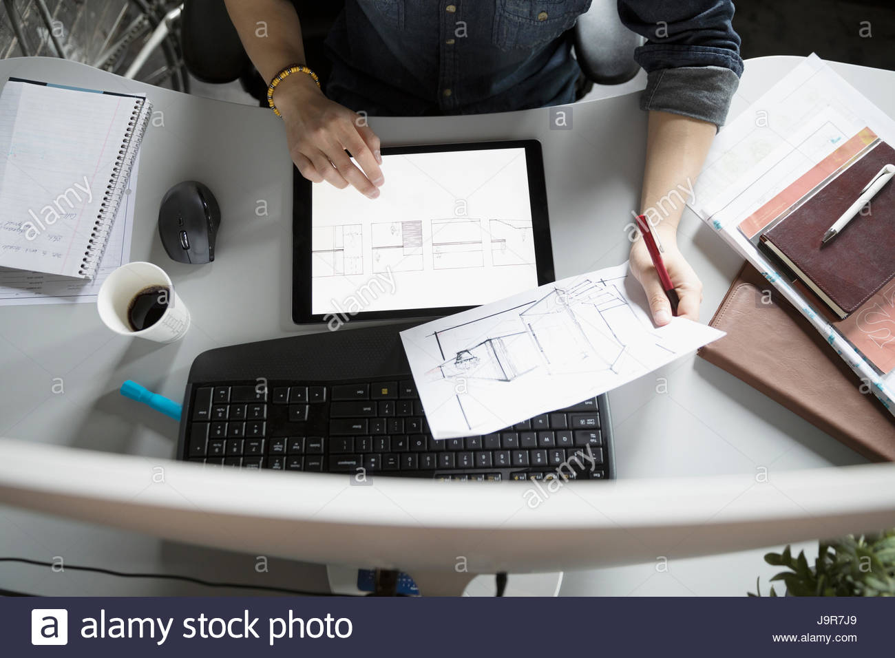 View from above male architect with digital tablet reviewing blueprints at desk - Stock Image