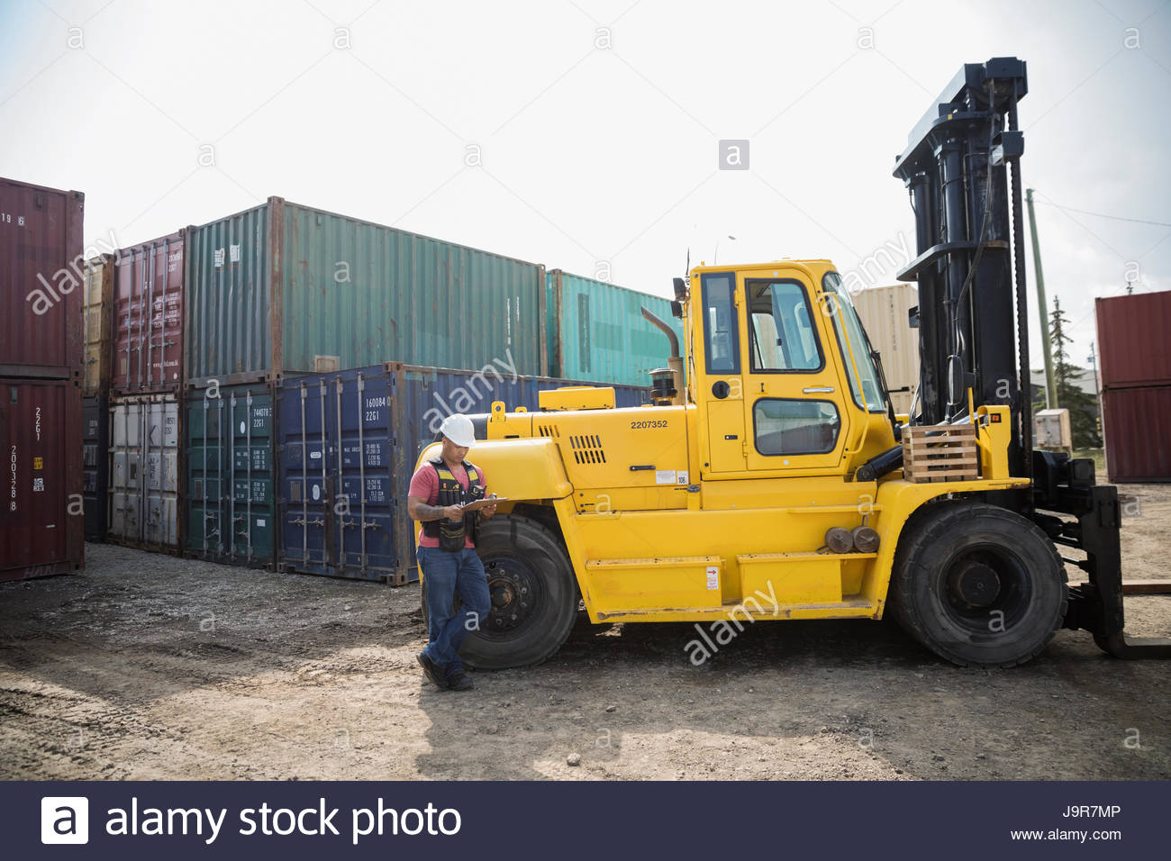 Male worker with clipboard leaning on forklift in sunny industrial container yard - Stock Image