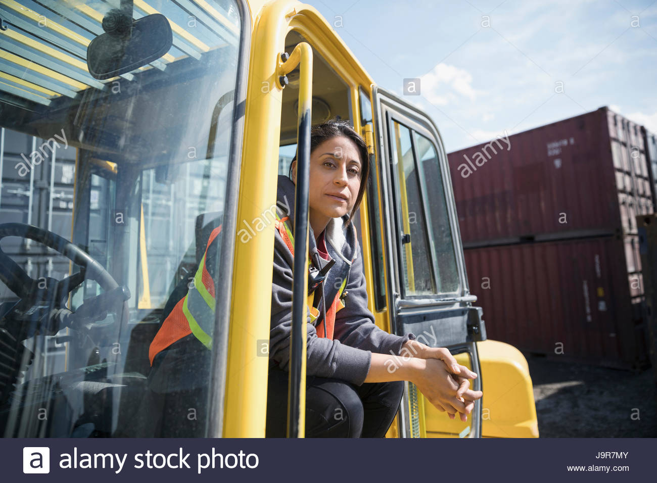 Portrait confident female forklift driver in sunny industrial container yard - Stock Image