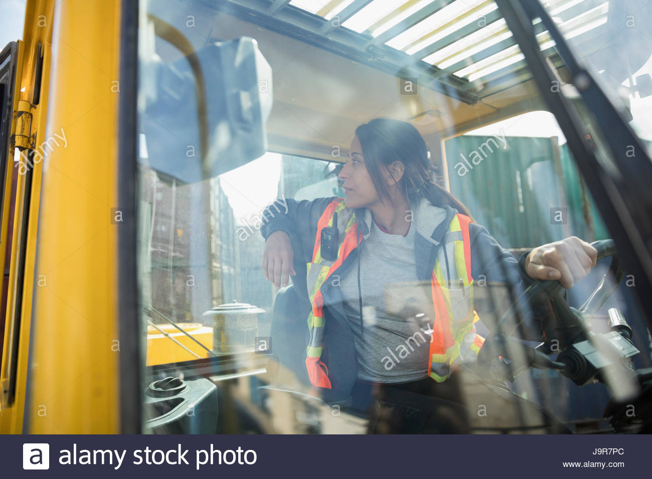 Female forklift driver inside forklift in industrial container yard - Stock Image