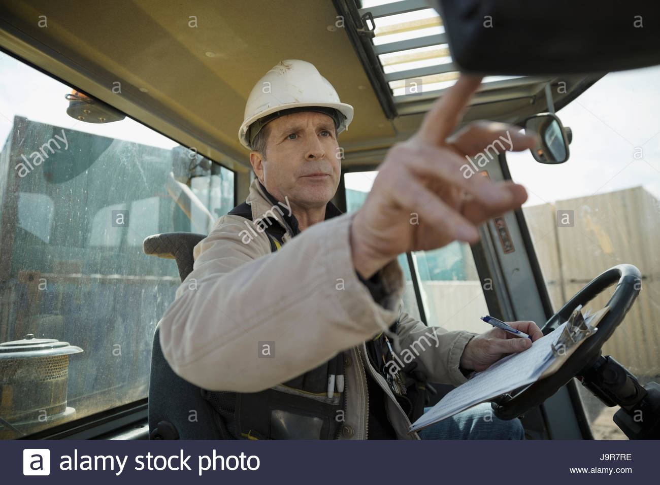 Male forklift driver with clipboard inside forklift in container yard Stock Photo