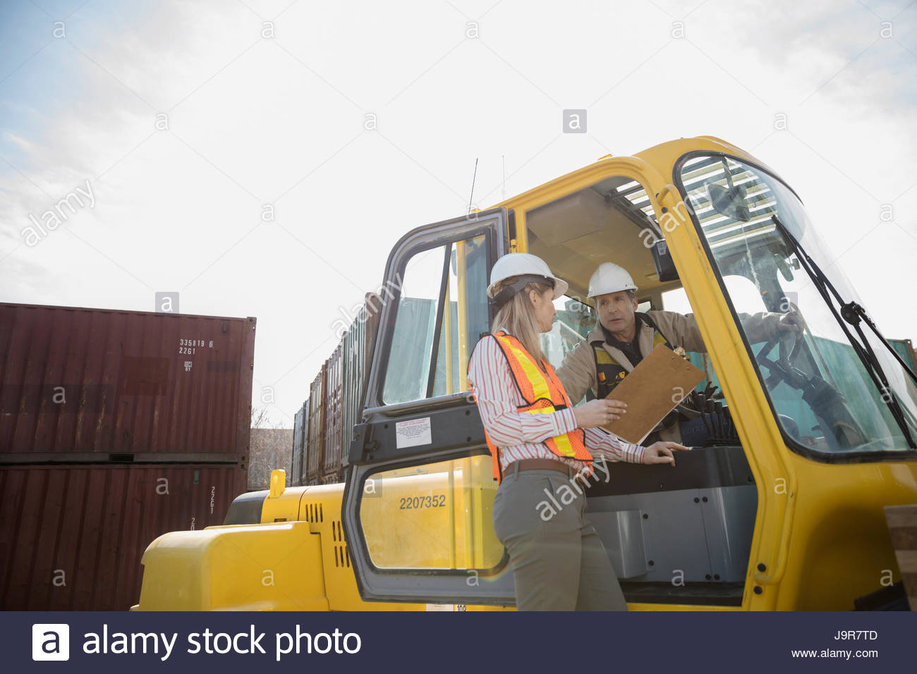 Female foreman with clipboard and forklift driver talking in sunny industrial container yard - Stock Image