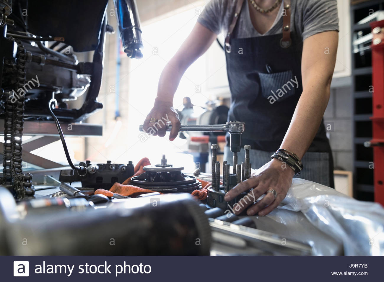 Female motorcycle mechanic using tools in auto repair shop - Stock Image