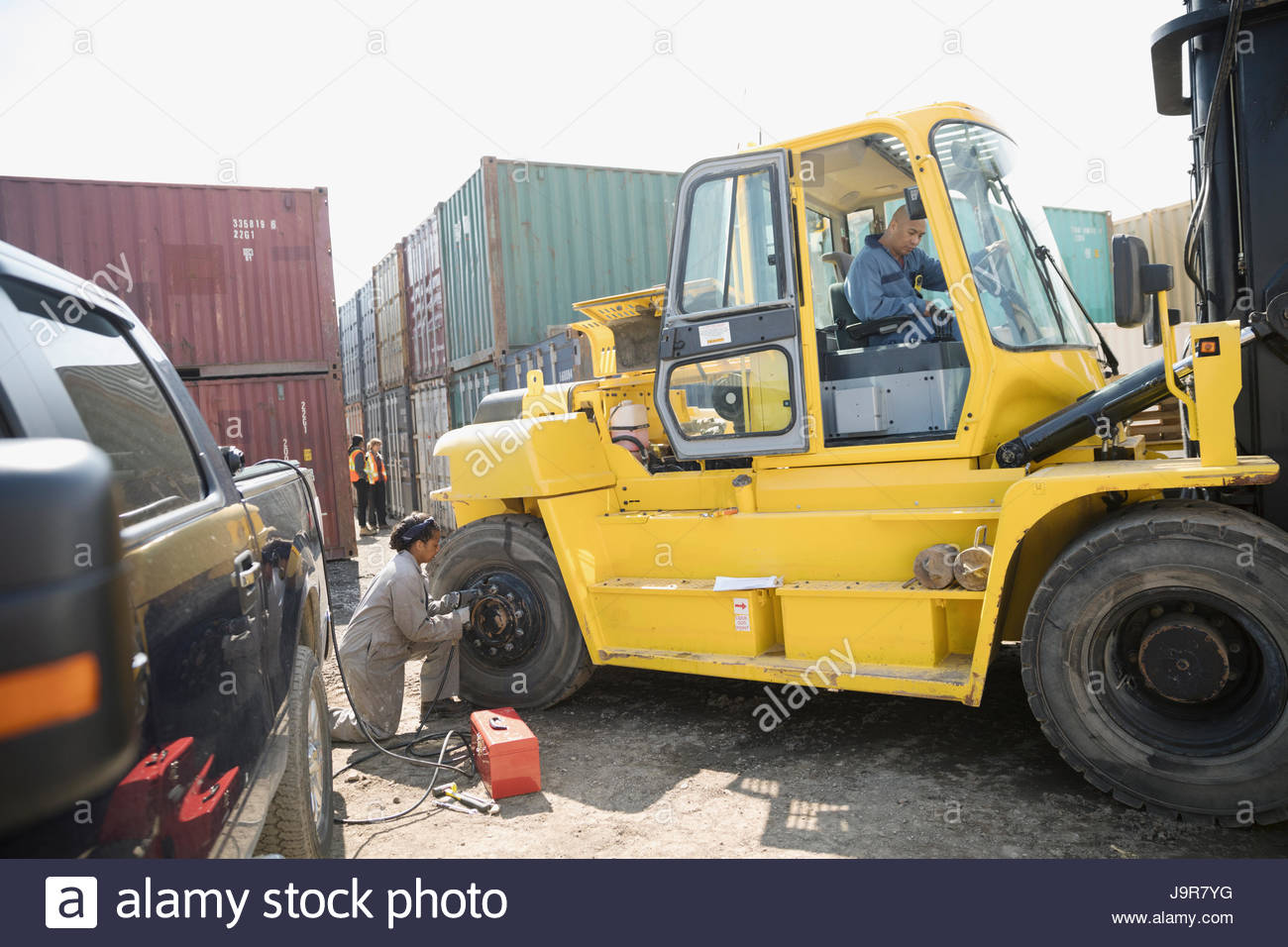 Mechanics fixing heavy machinery in sunny industrial container yard - Stock Image