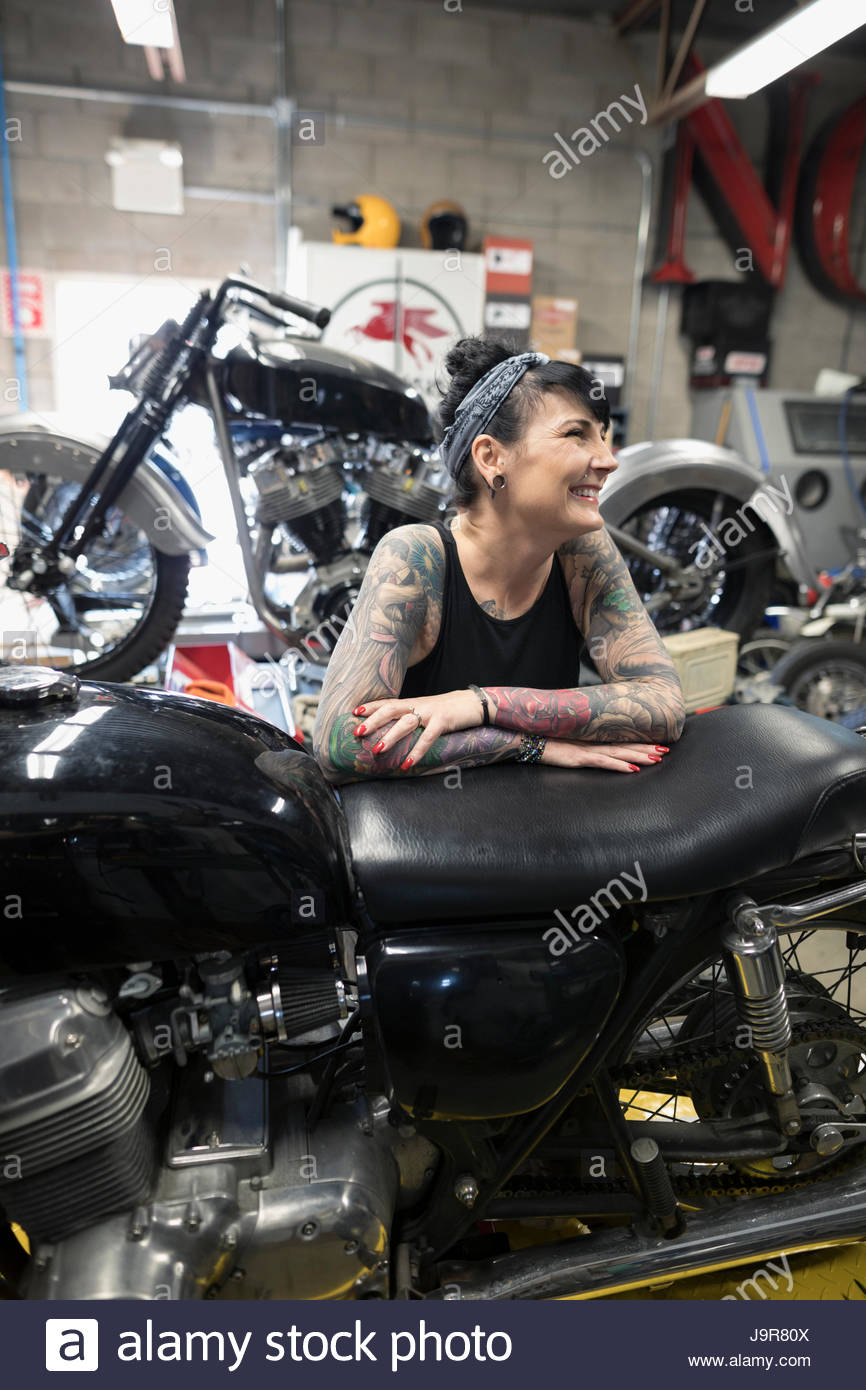 smiling female motorcycle mechanic with tattoos in auto repair shop