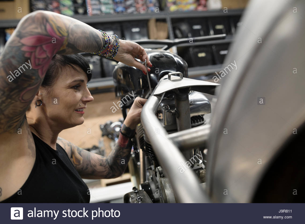 Female motorcycle mechanic with tattoos fixing motorcycle in auto repair shop - Stock Image