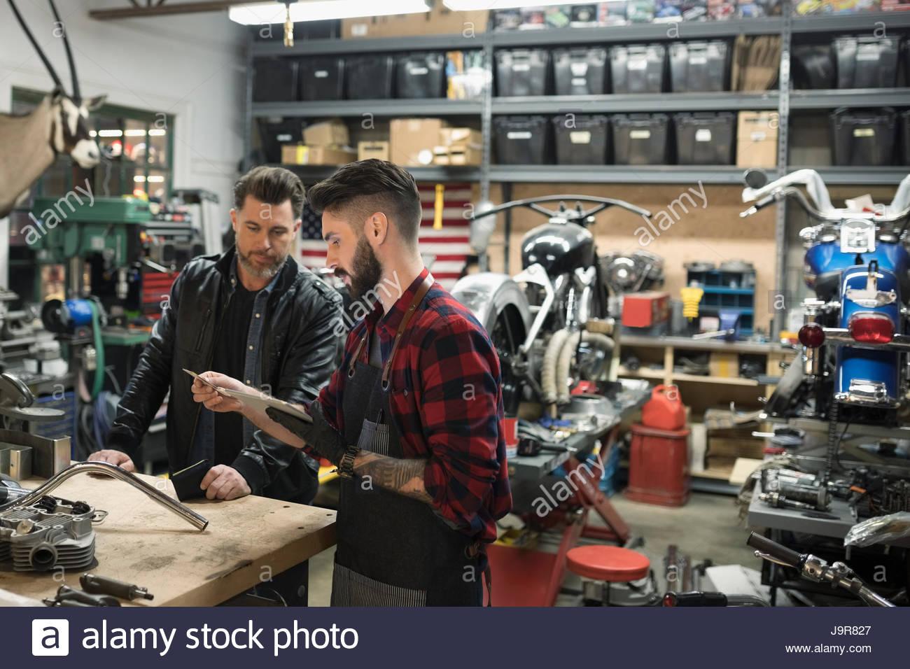 Motorcycle mechanics examining parts in auto repair shop - Stock Image