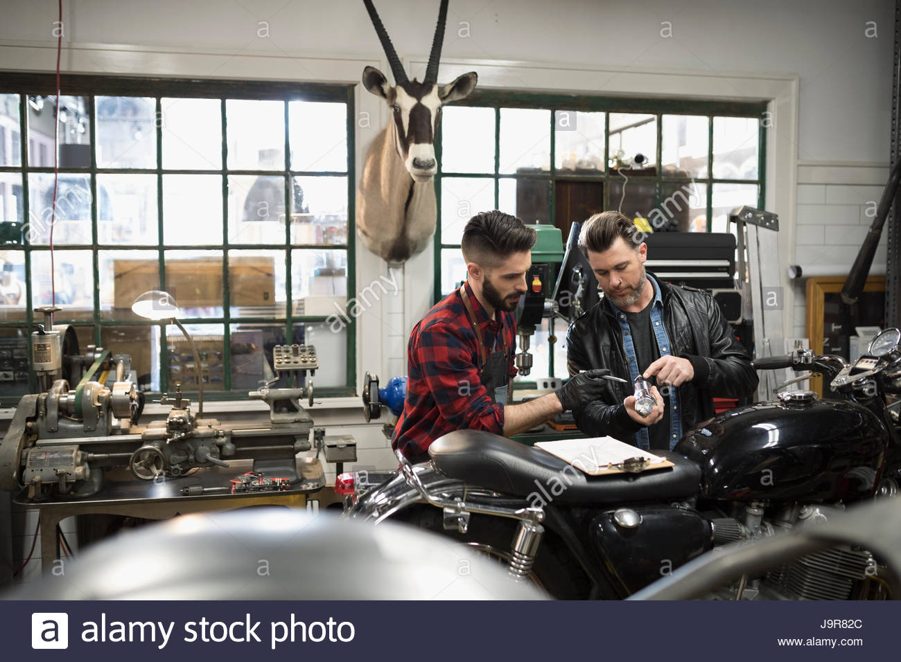 Motorcycle mechanics with clipboard examining part, fixing motorcycle in auto repair shop - Stock Image