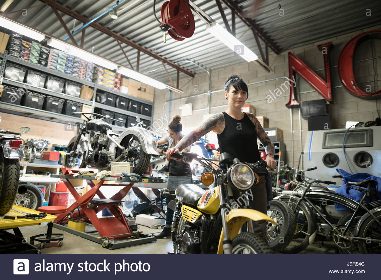 portrait confident female motorcycle mechanic pushing motorcycle in auto repair shop