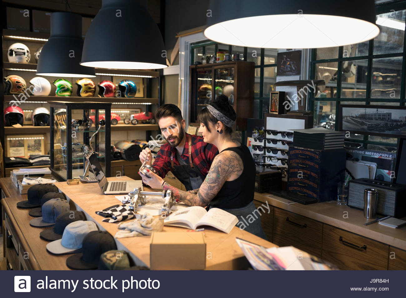 Motorcycle mechanic shop owners examining parts behind counter - Stock Image