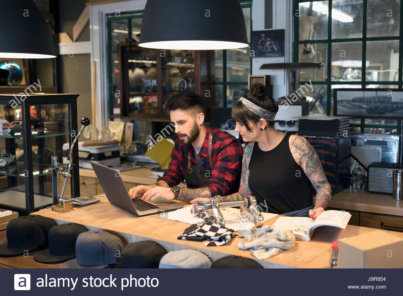 Motorcycle mechanic shop owners order parts at laptop behind counter - Stock Image