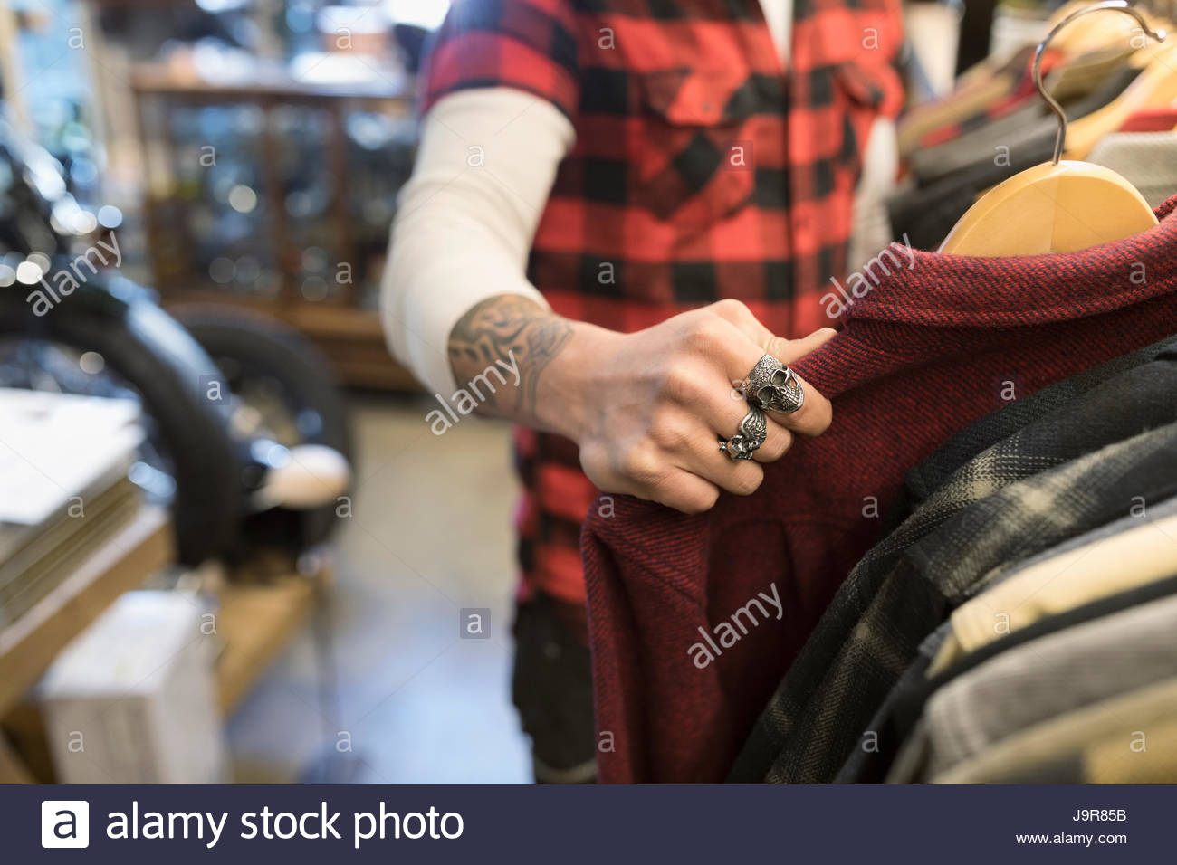 Male customer with tattoo and rings shopping, browsing at clothing in shop - Stock Image