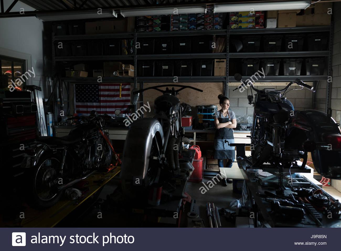 Pensive female motorcycle mechanic working behind motorcycles in auto repair shop - Stock Image