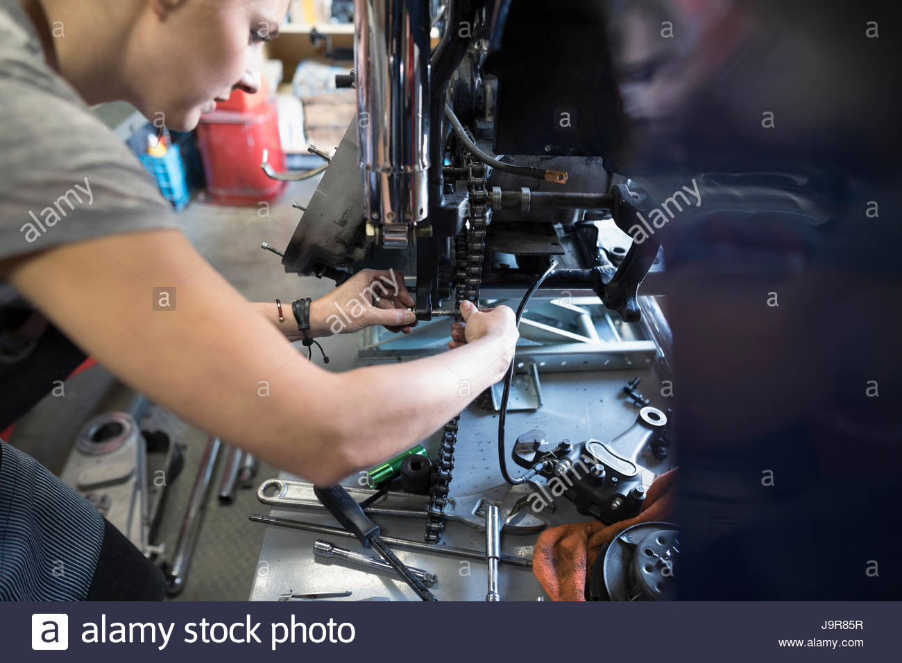Female auto mechanic fixing motorcycle in auto repair shop - Stock Image