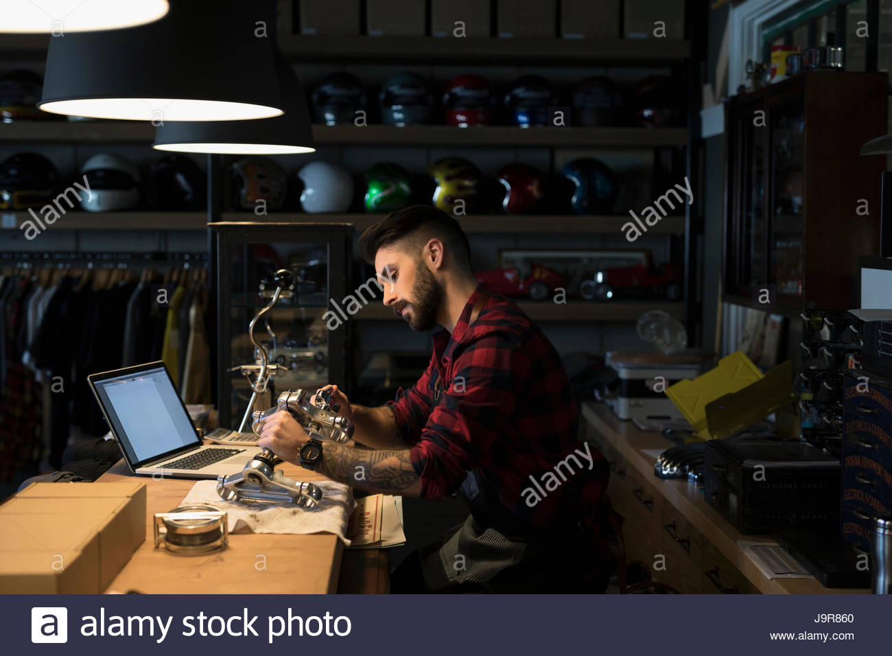 Motorcycle mechanic shop owner fixing part, working late behind counter - Stock Image