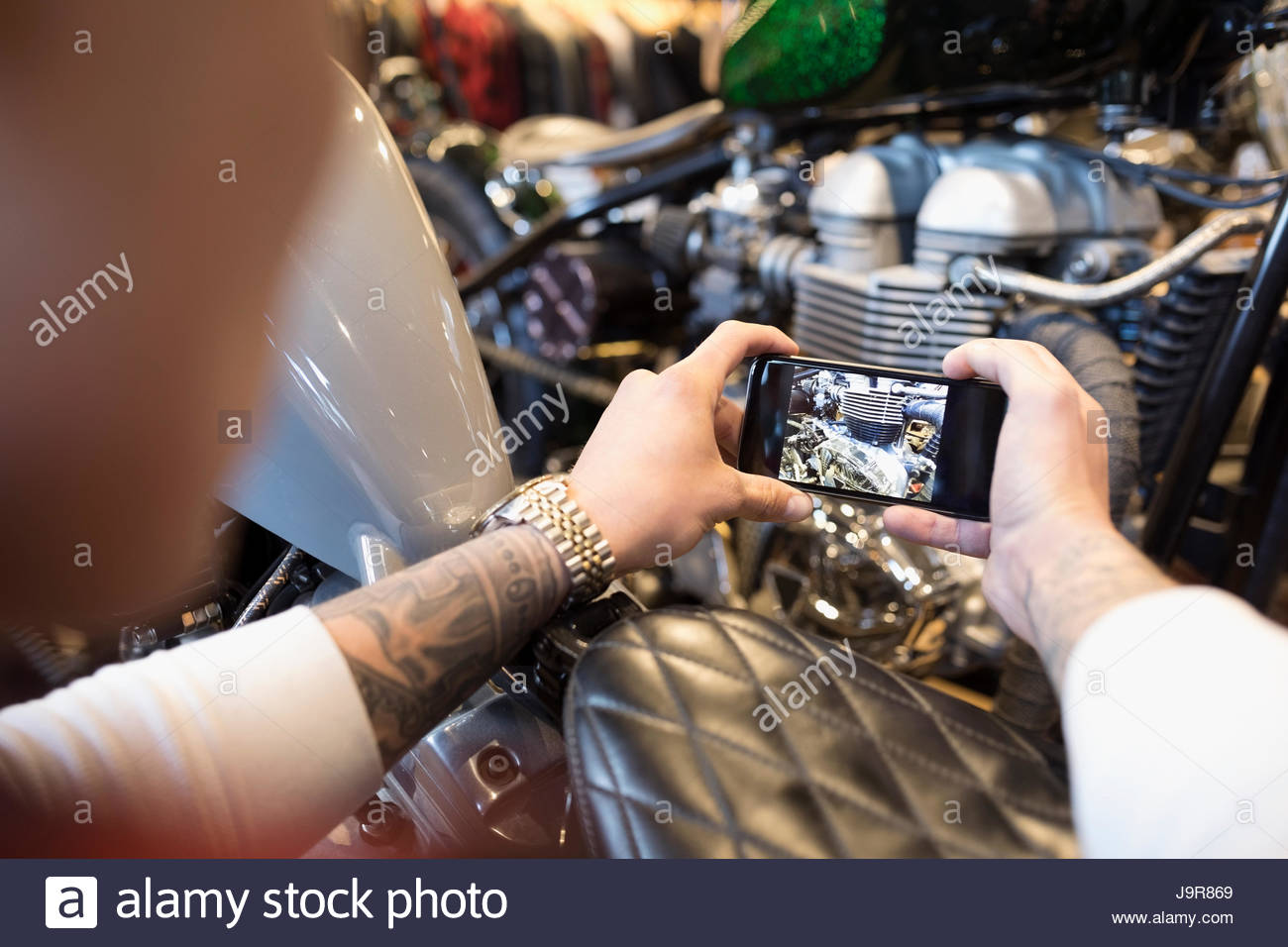Personal perspective motorcycle mechanic with camera phone photographing engine - Stock Image