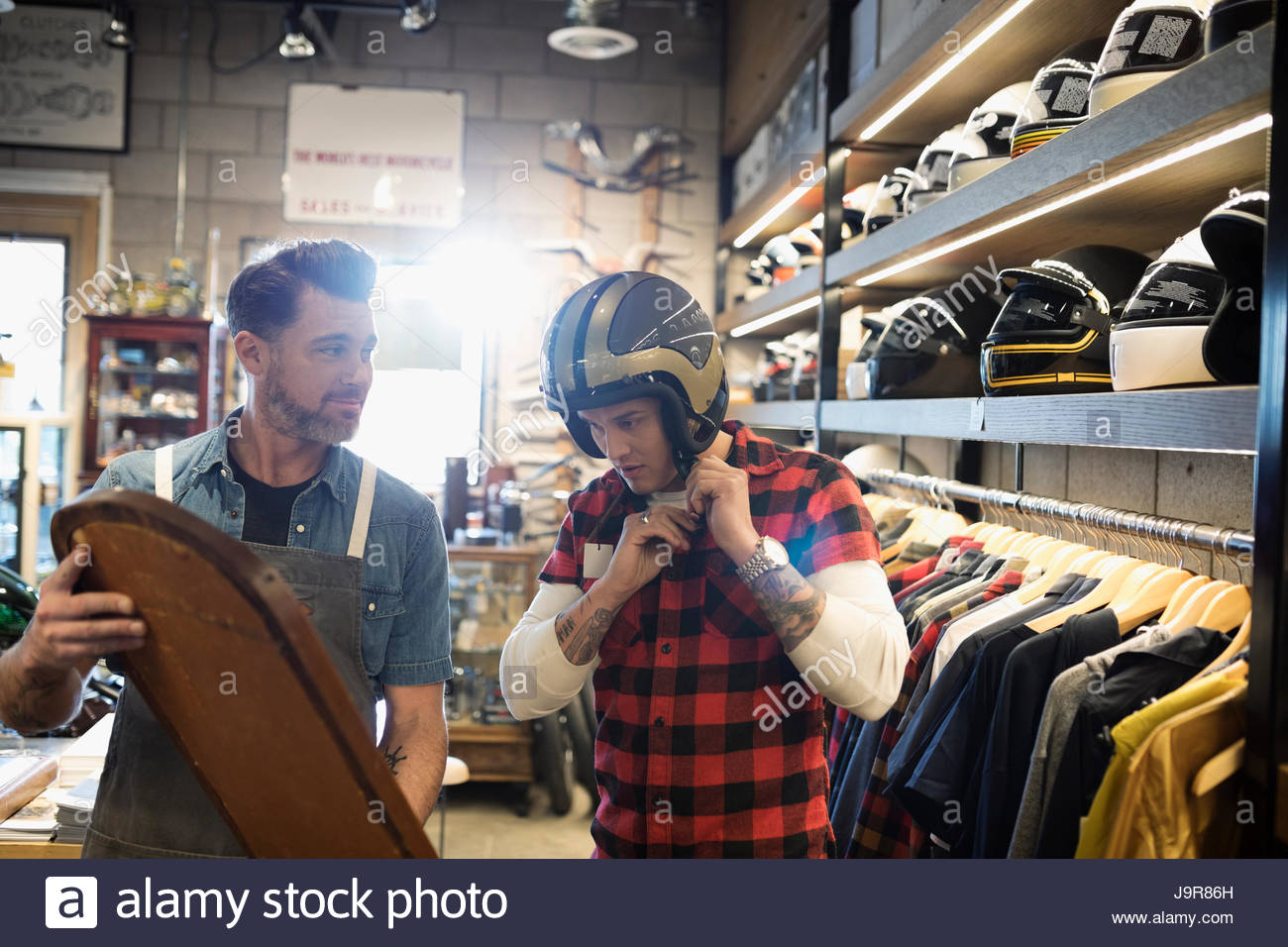 Motorcycle shop owner holding mirror for customer trying on helmet - Stock Image