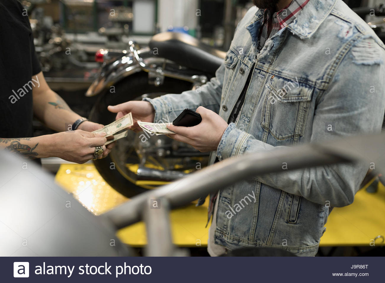 Customer paying motorcycle mechanic with cash in auto repair shop - Stock Image