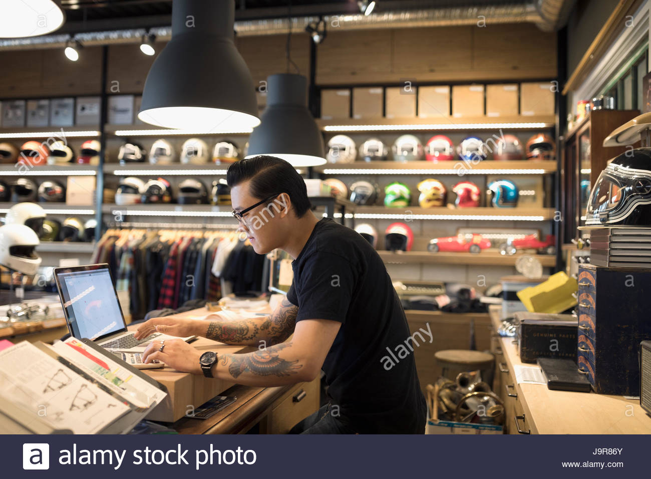 Motorcycle shop owner working at laptop behind counter - Stock Image