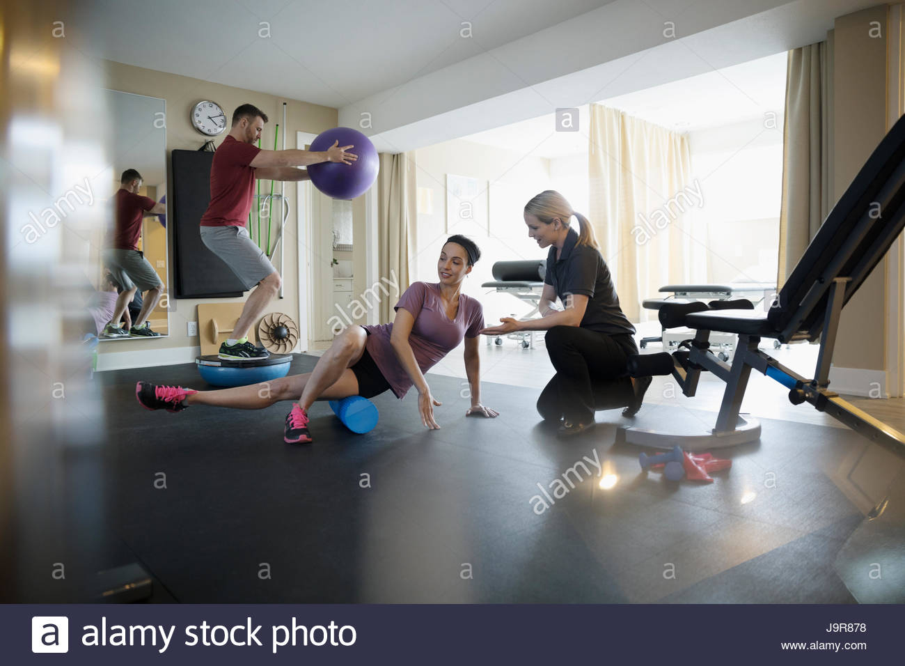 Female physiotherapist working with clients exercising and stretching in clinic gym - Stock Image