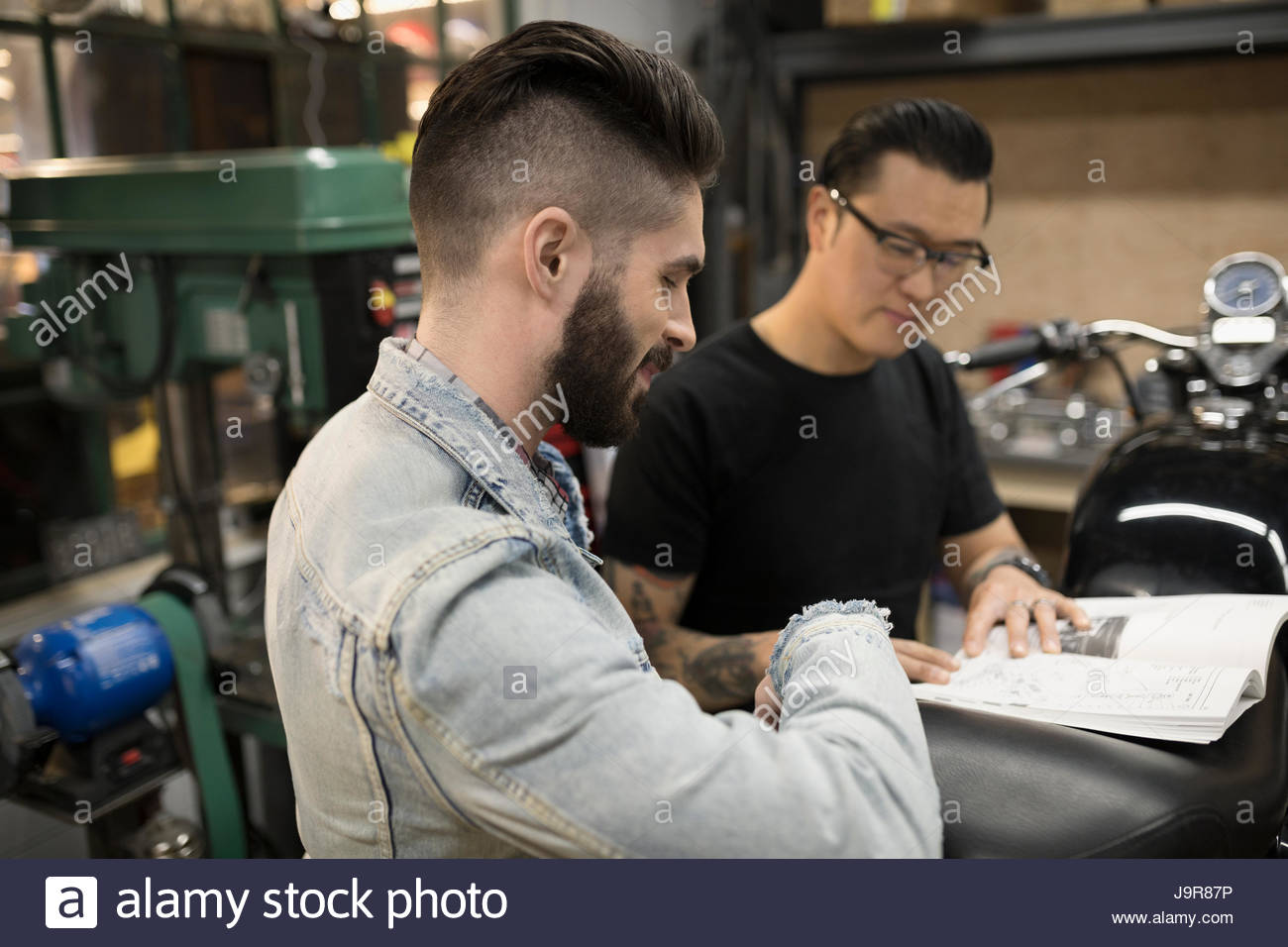 Motorcycle mechanics looking at part catalog in auto repair shop - Stock Image